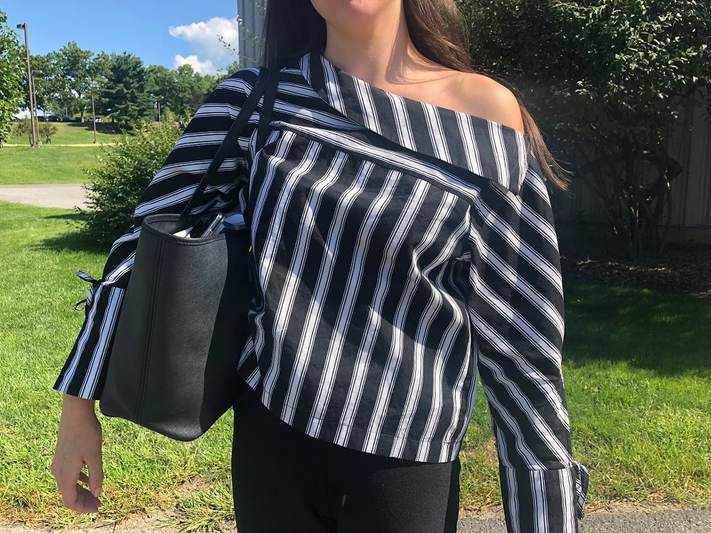 Georgia wears a black and white striped off-the-shoulder top with bell sleeves.