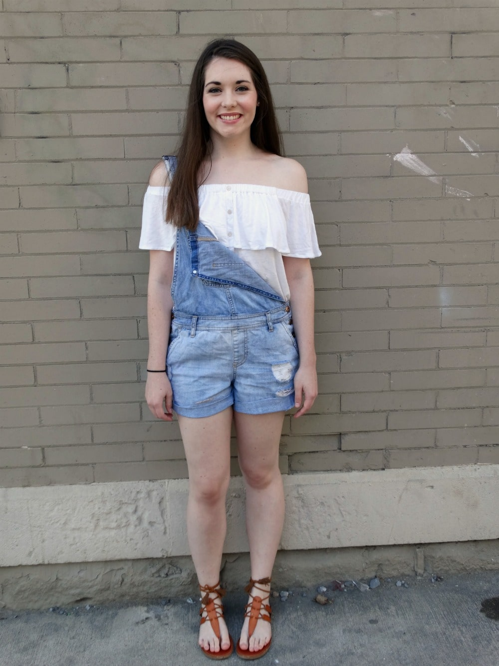 College student at West Virginia University wears an off-the-shoulder top with overall shorts for casual summer style.