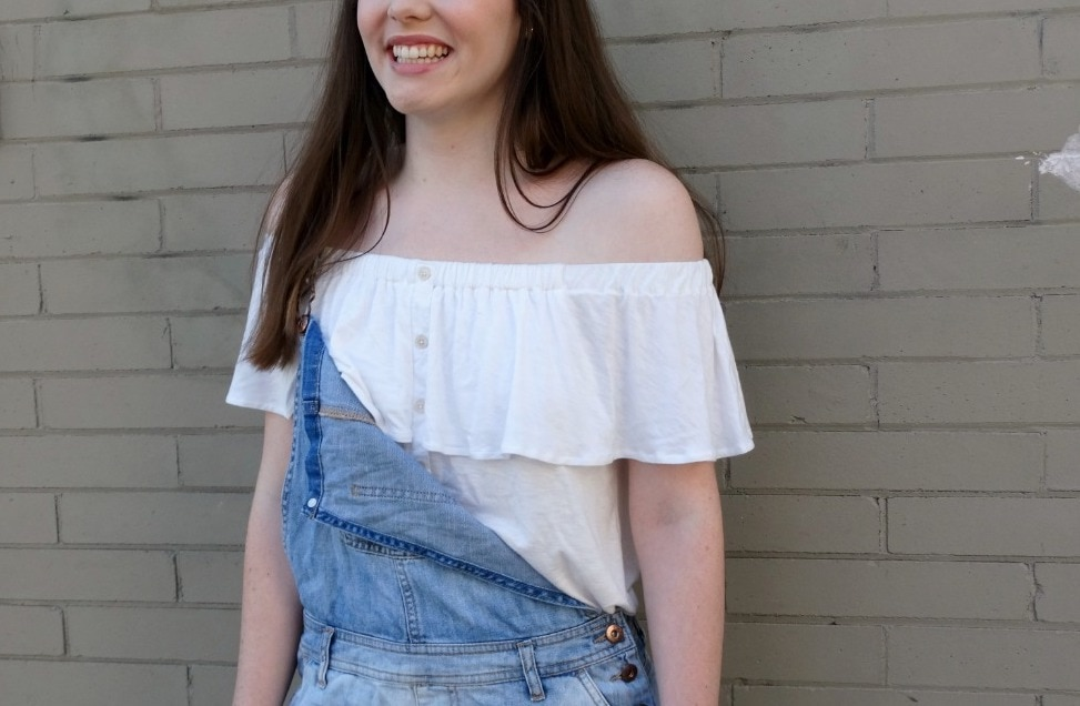 Off-the-shoulder white blouse pairs with light-wash denim overalls for a bohemian vibe.