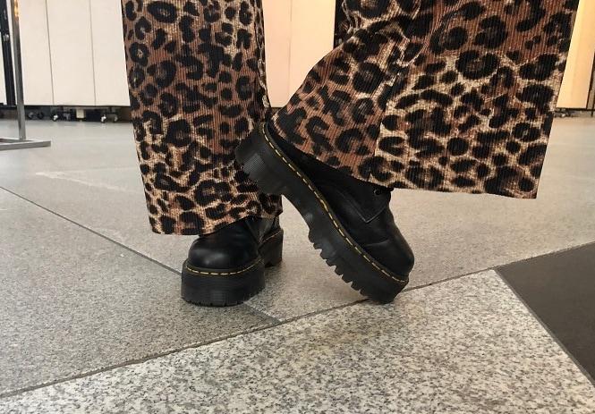 Hannah wears platform black Doc Marten sneaker boots.