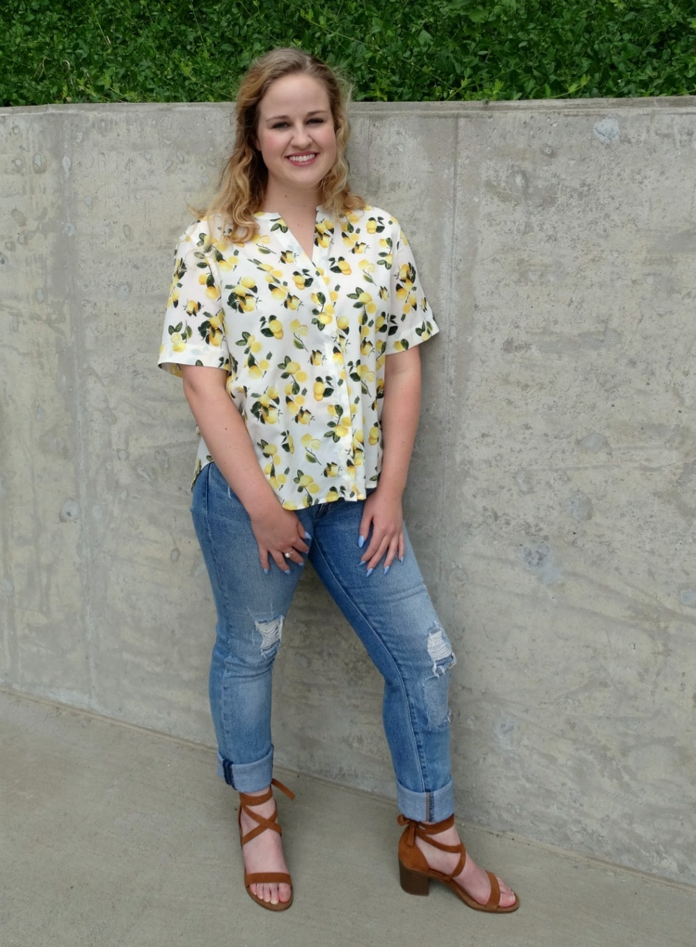 Student style on campus: lemon print short sleeved button up blouse paired with light-wash distressed denim jeans and brown lace-up sandals.