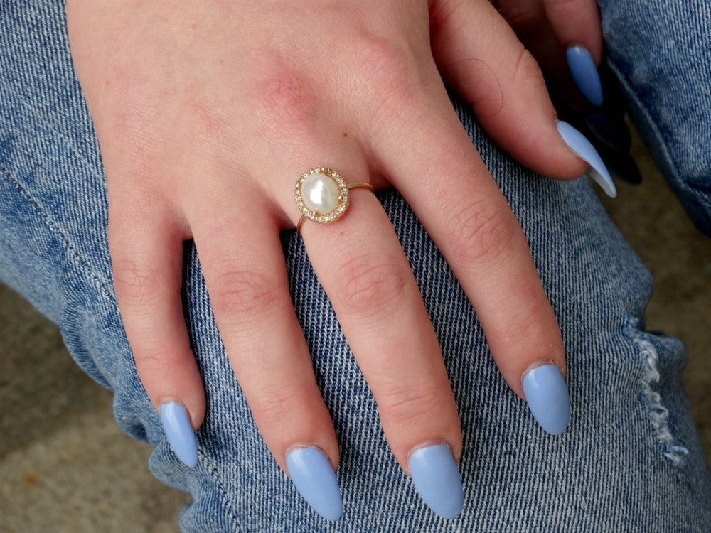 West Virginia University student wears baby blue fingernail polish on her long curved fingernails with a dainty gold and pearl ring.