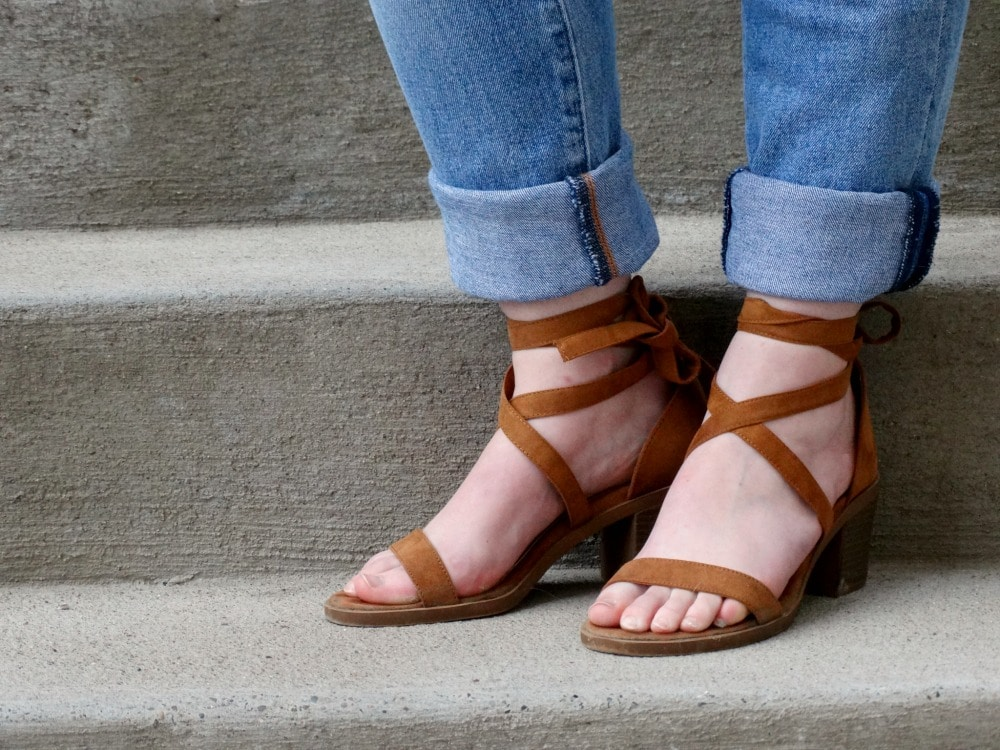 Cuffed jeans show off strappy brown sandals with a chunky heel.