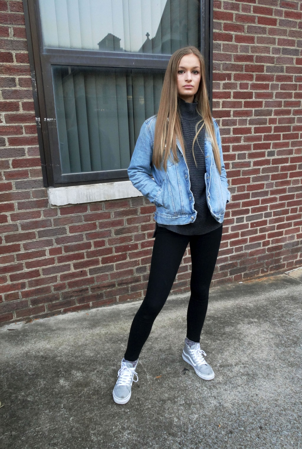 This student wears a space grey turtleneck sweater with an oversized, distressed denim jacket, black leggings, and sporty grey sneakers with white detailing.