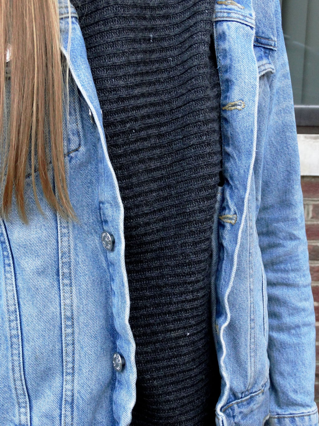 A West Virginia student wears a baggy ribbed cotton turtleneck grey sweater with a light-wash distressed denim jacket.