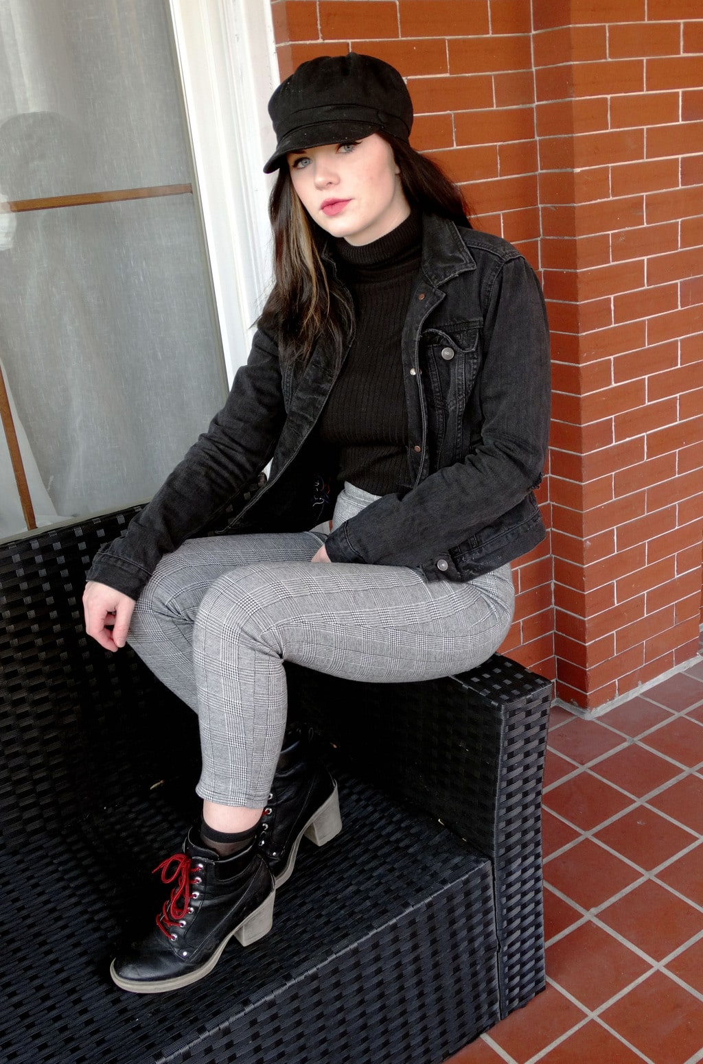 West Virginia University student wears a black turtleneck sweater with white and grey checkered pants, lace up chunky-heeled booties, a distressed dark grey denim jacket, and a black cabby hat.
