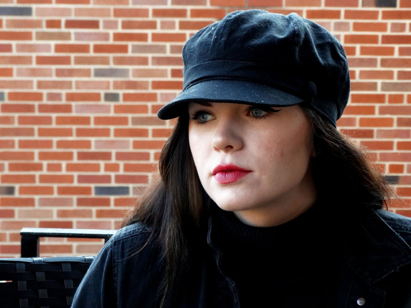 Mackenzie wears a black cabby hat with dramatic cat eyeliner and a bold pink lip.