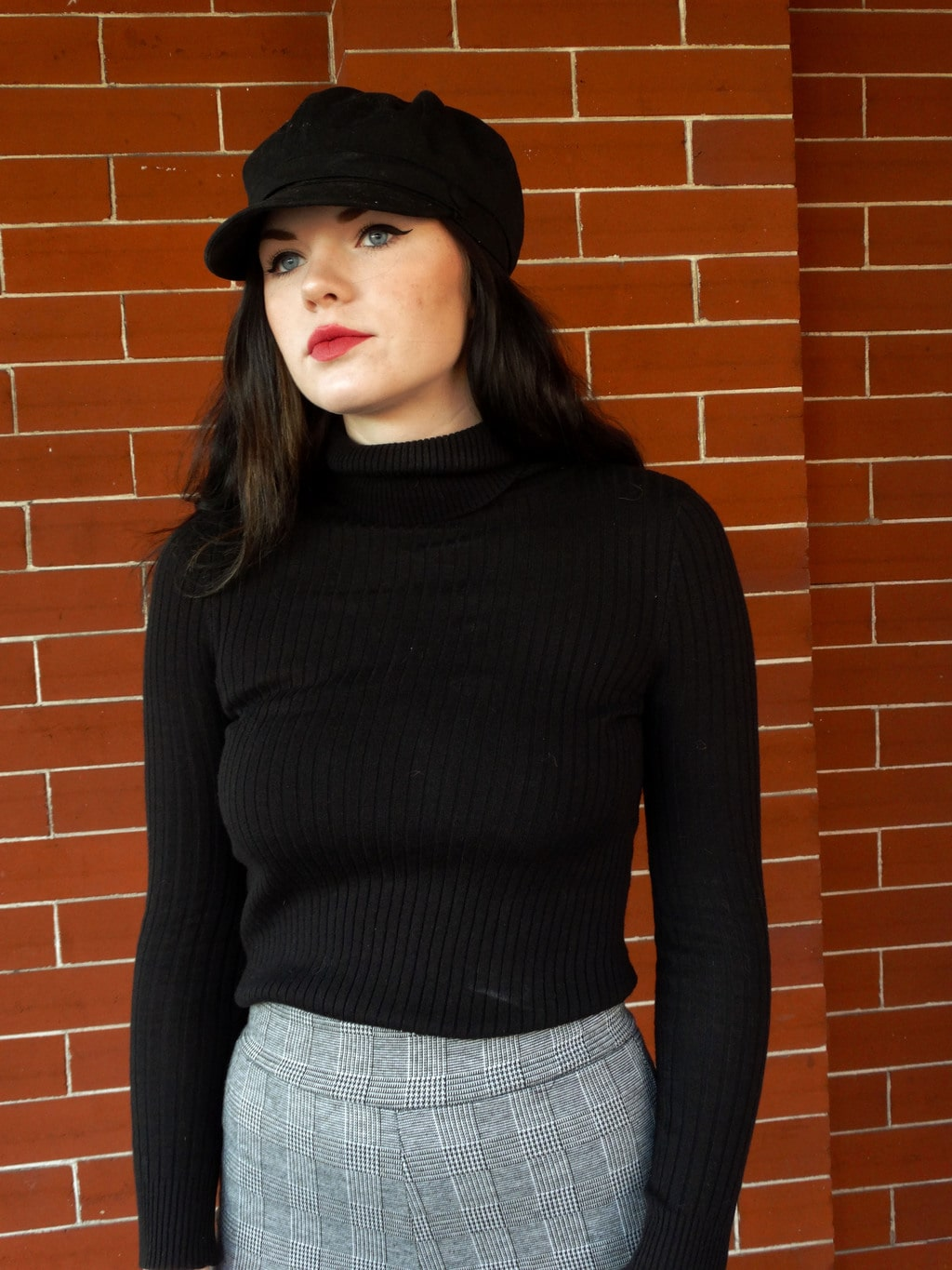 Mackenzie styles a tight black turtleneck sweater with high-waisted checkered pants and a black cabby hat.
