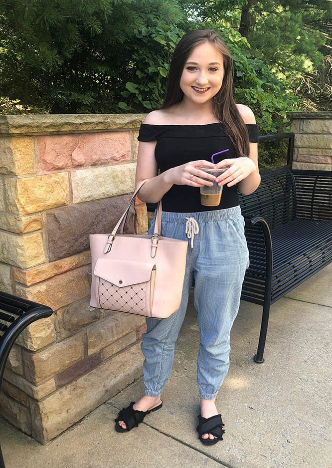 West Virginia University student Maggie wears a black off-the-shoulder fitted top tucked into blue and white drawstring jogger pants with black frayed slide sandals and a pink Michael Kors tote.