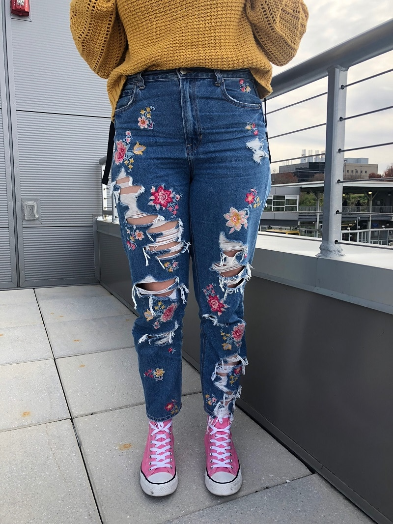 Maria's high-waisted jeans are ripped and embroidered with colorful flowers.