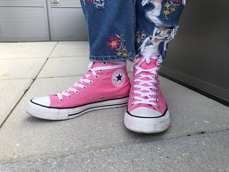 WVU student Maria wears high-top neon pink Converse sneakers.