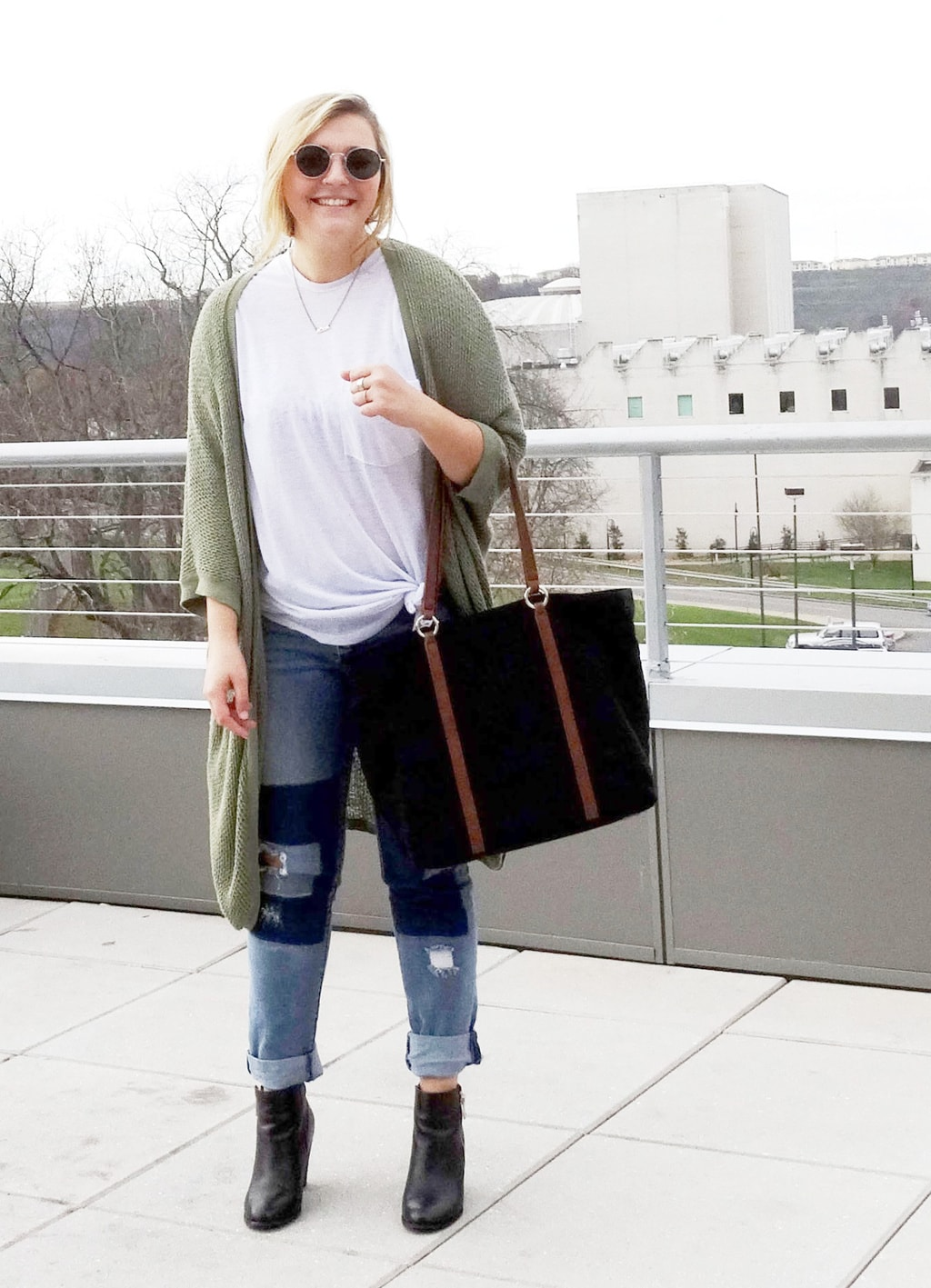 WVU college student Mel shows off her campus street style, wearing the perfect patchwork jeans outfit. Includes a white tee, boyfriend jeans, and an olive cardigan with heeled ankle booties