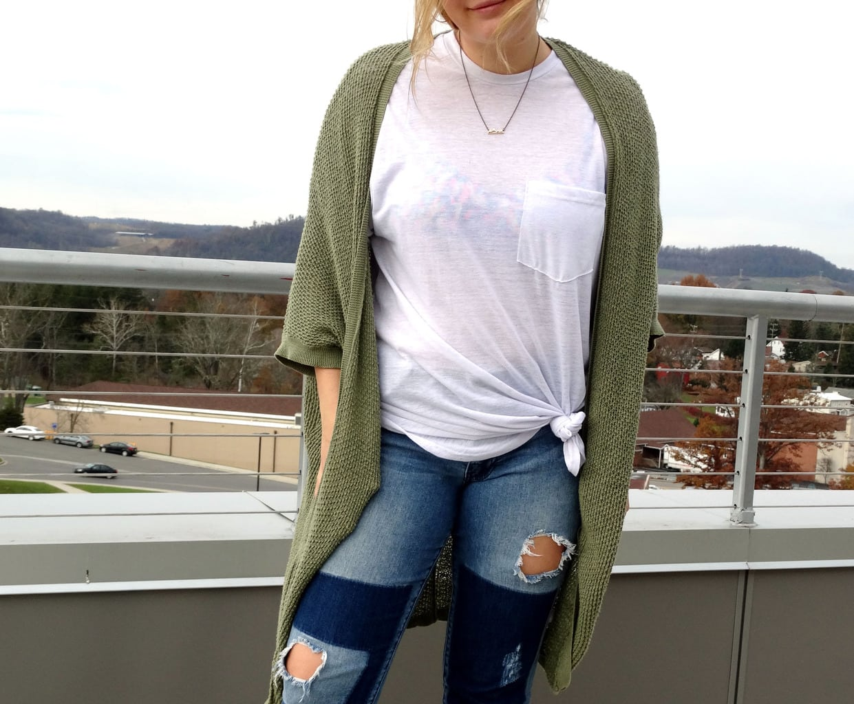 Mel wears a loose-fitted white pocket tied t-shirt with a cozy forest green cardigan.
