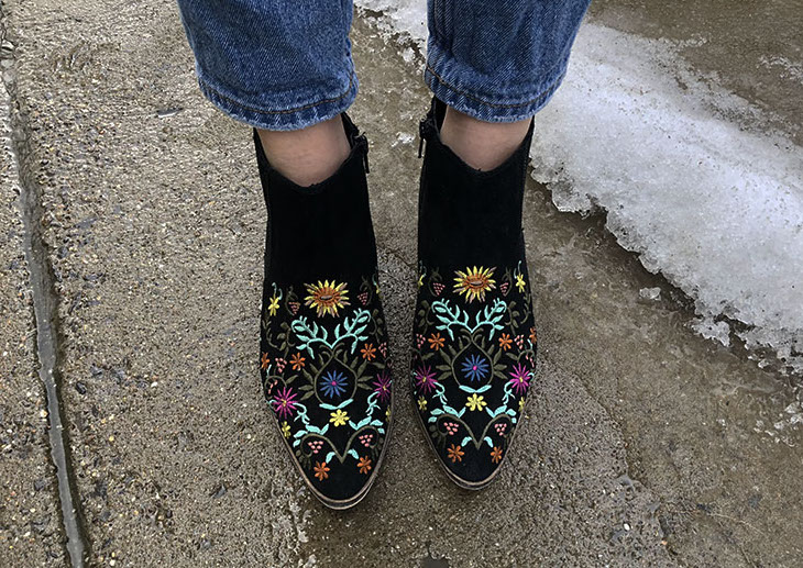 Morgan wears black booties with blue, yellow, purple, and brown floral embroidery.