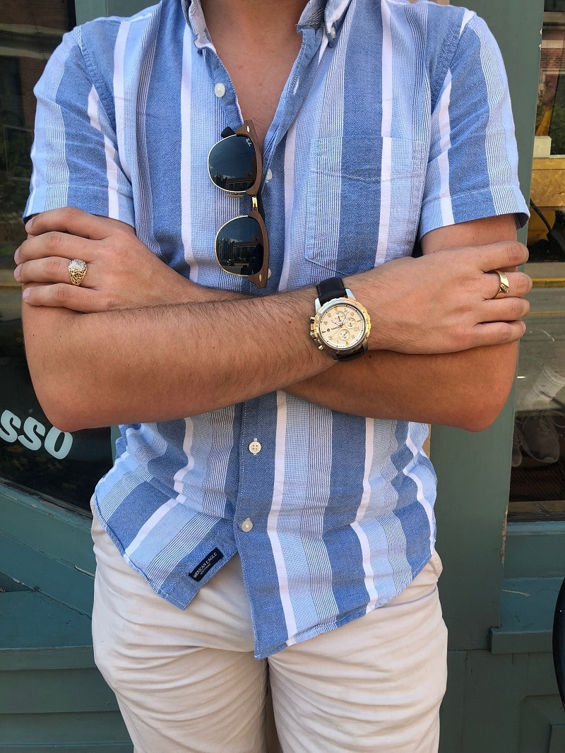 Nathan pairs his blue button-up shirt with hand-me-down silver rings, a large-face Fossil watch with a dark brown leather band, and Ray-Ban Clubmasters.