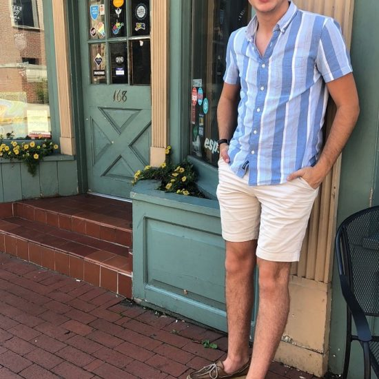 Nathan wears a summery collared button-up with various shades of blue and white vertical stripes, Ray-Ban sunglasses, khaki shorts, and brown leather Sperry boat shoes.