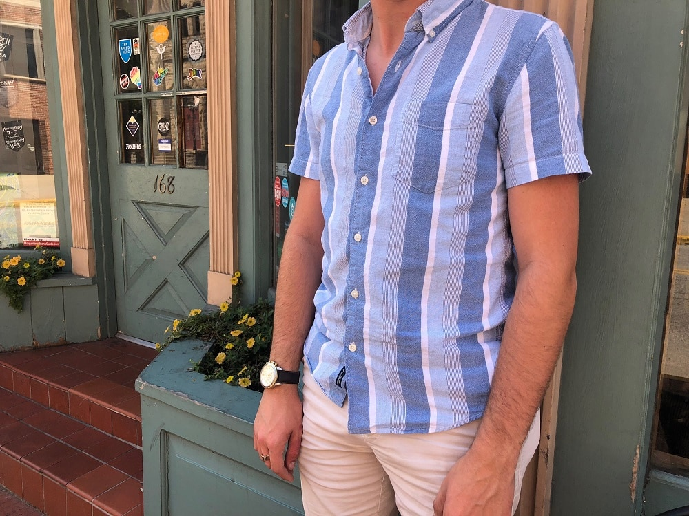 Nathan wears a button-up with vertical blue and white stripes of assorted dimensions, shades, and sizes.