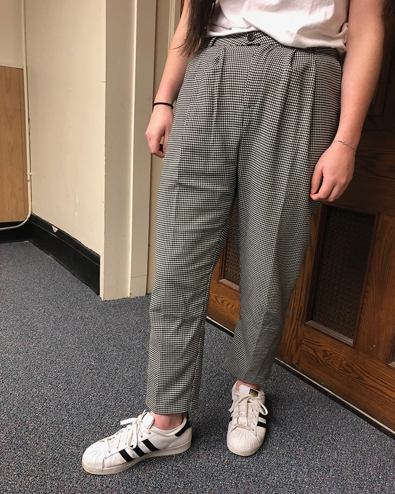 This WVU student wears high-waisted loose-fitted grey and white checkered slacks with her classic Adidas sneakers.