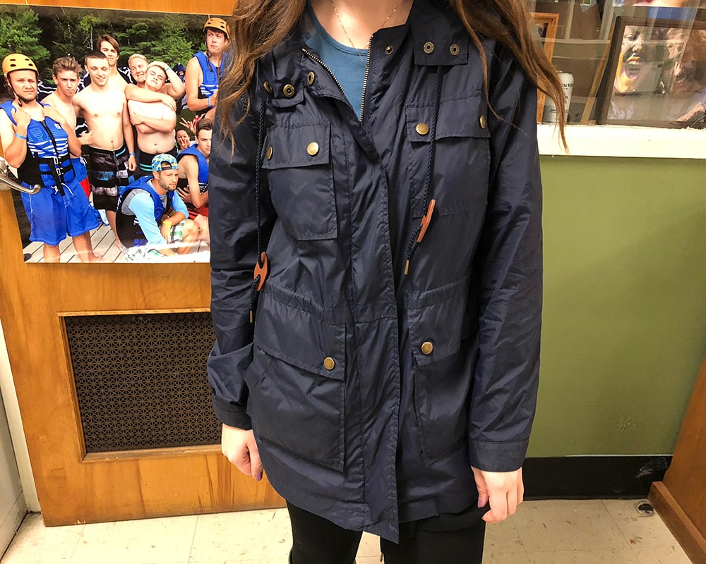 Sarah stays dry in a navy blue anorak jacket with gold buttons and details.