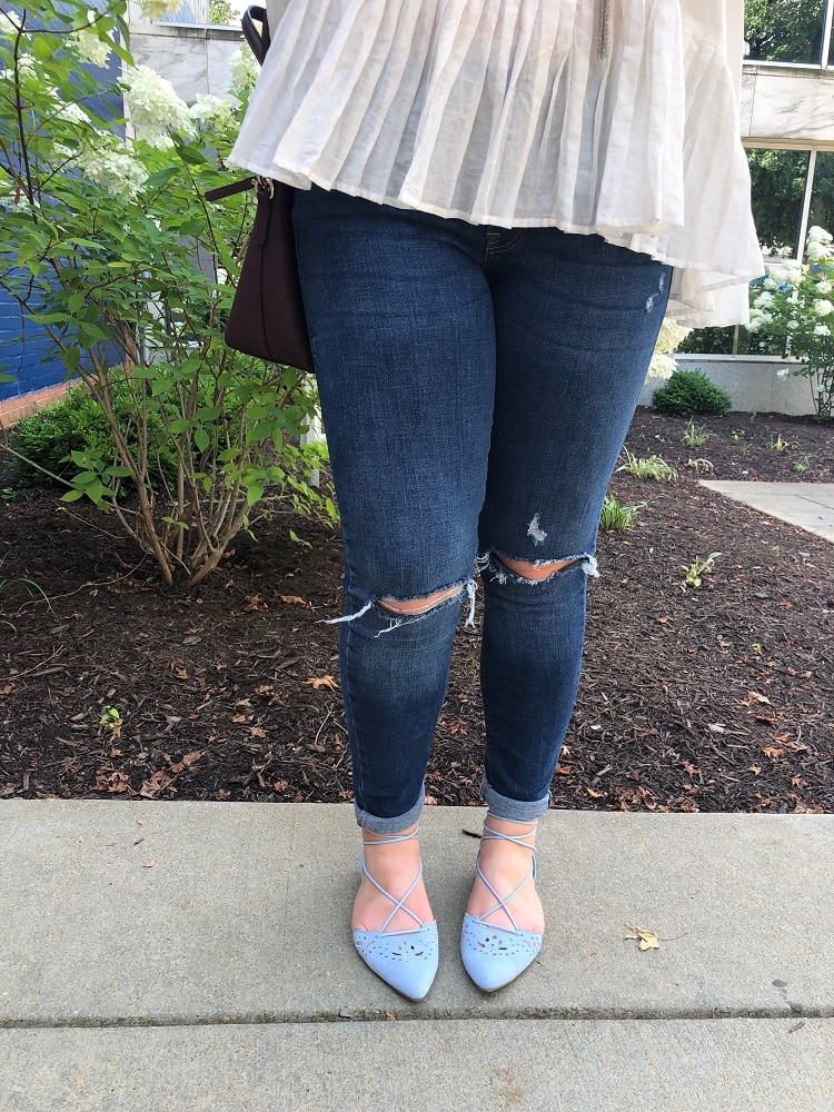 Sarah sports dark-washed distressed denim jeans with baby blue pointed flats.