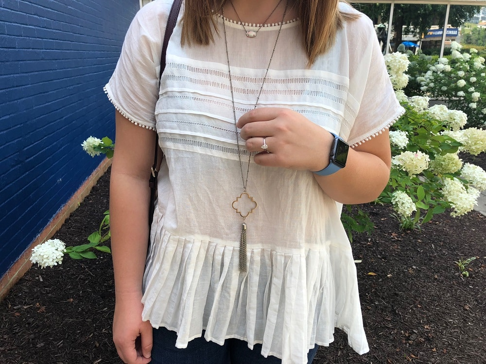 Sarah wears layered gold necklaces with tassles and gems.