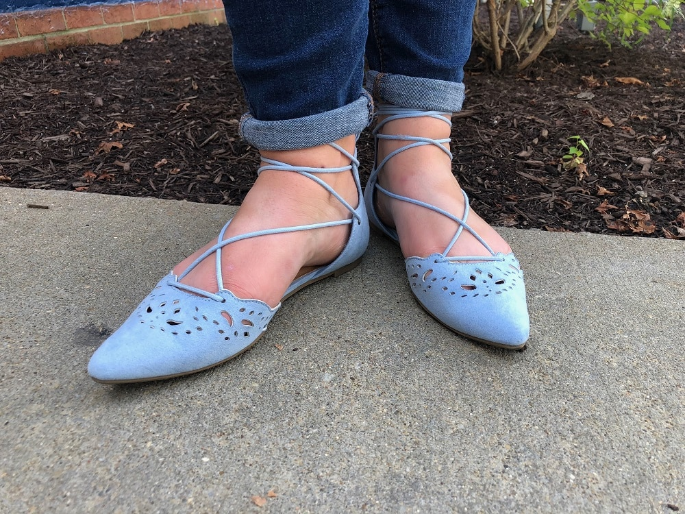 Sarah wears pointed-toe baby blue flats with ankle ties.