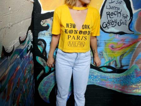Fashion at West Virginia University: Student Shelby rocks a trendy outfit consisting of a yellow v-neck tee with cutout detail that reads New York Paris London Milan, light wash mom jeans, black sandals, and round yellow sunglasses