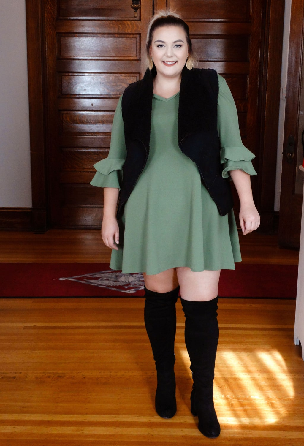 Sydney wears a green dress with layered ruffle bell sleeves and a black furry vest with black over-the-knee boots.