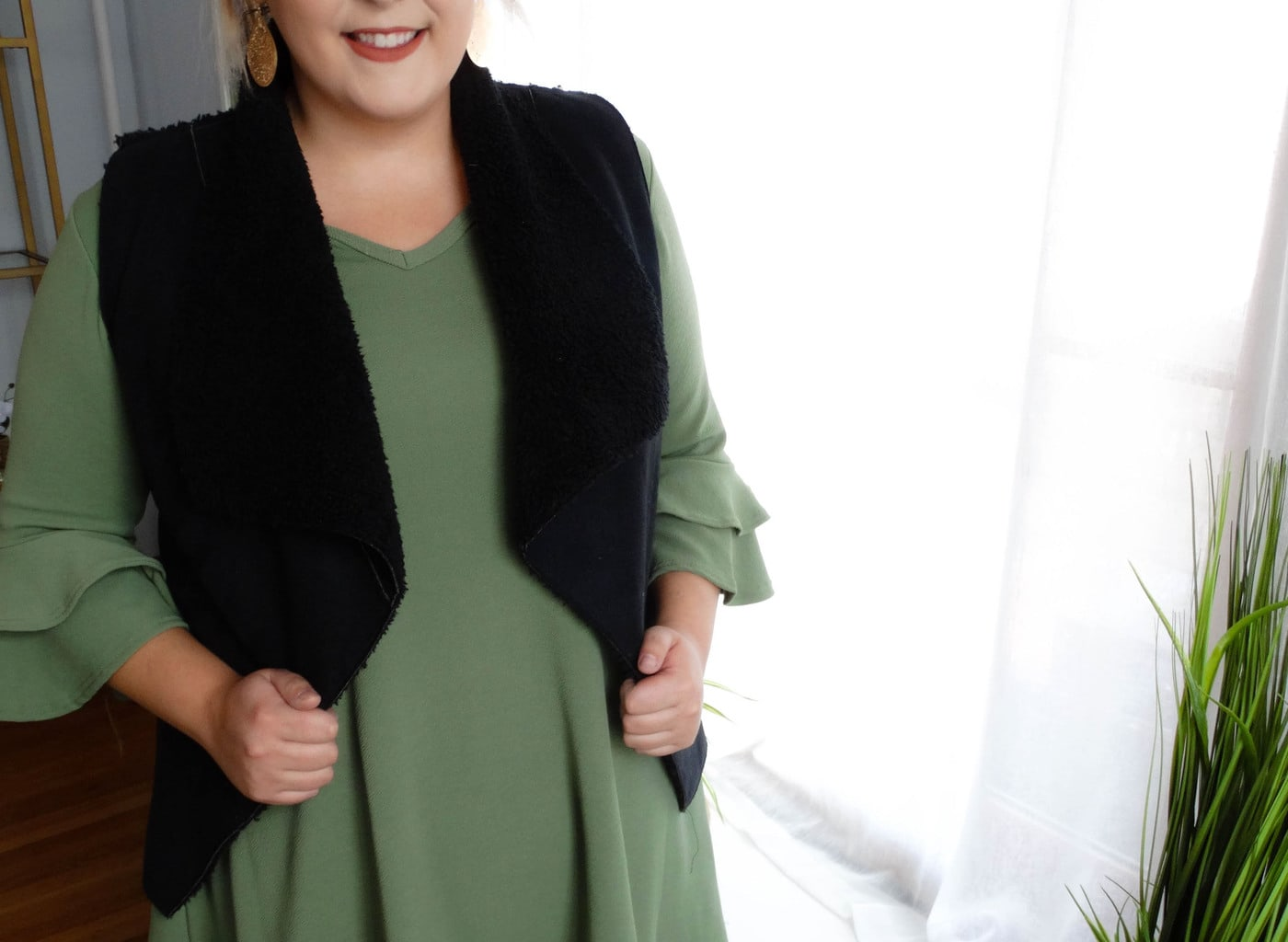 West Virginia University student Sydney wears a green dress with layered ruffled sleeves and a black furry vest.
