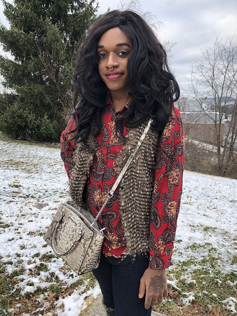 Teddy wears a bright red button-up blouse with a loud paisley print. He pairs it with a brown and black striped faux fur vest and a Michael Kors cream snakeskin crossbody purse.