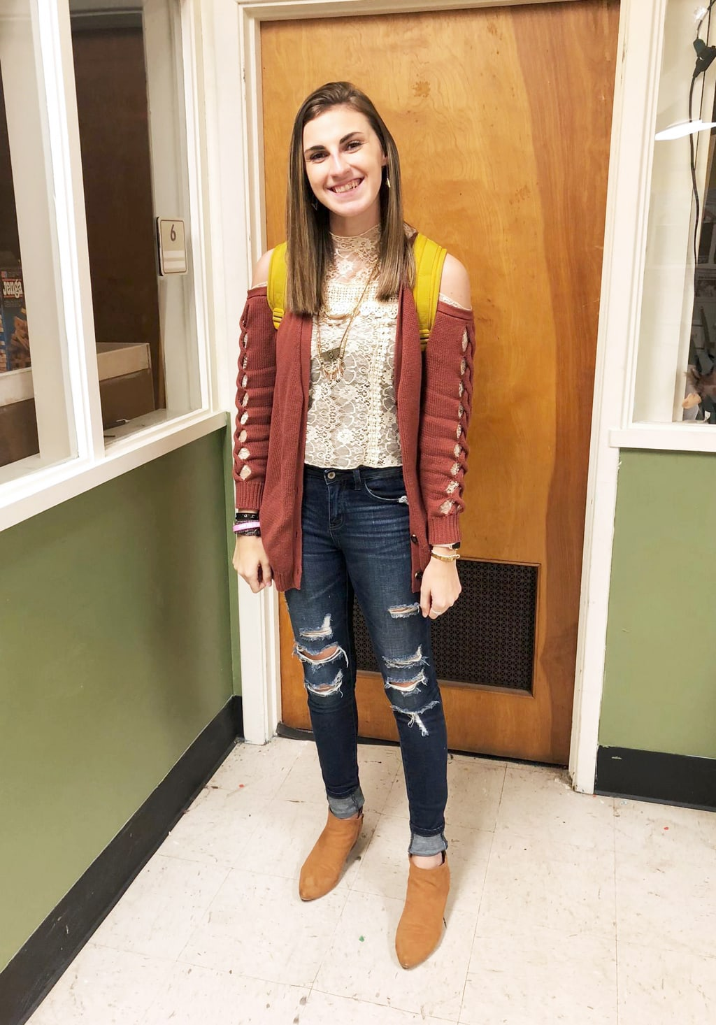 Gentry, a student at West Virginia University, wears a cropped lace high neck blouse with an open shoulder maroon cardigan and ripped jeans.