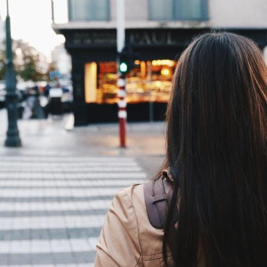 Photo of brunette girl wearing a tan jacket walking down a city street.