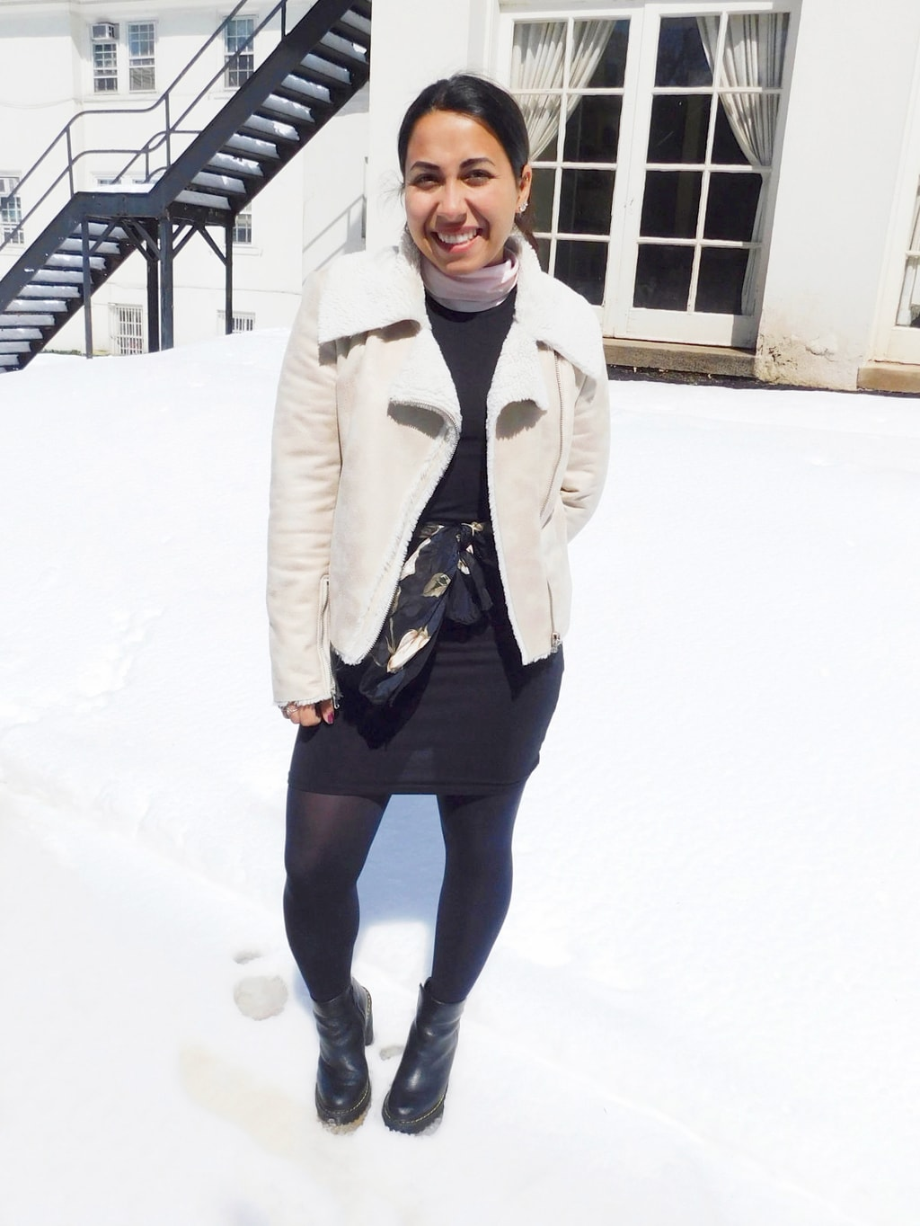 Jefferson University student Vanessa wears a springtime tank dress with a pastel pink long sleeve turtleneck underneath, opaque black tights, a white motorcycle style shearling-lined coat, a feminine black and pink scarf worn as a belt, and black rubber Doc Martens booties.