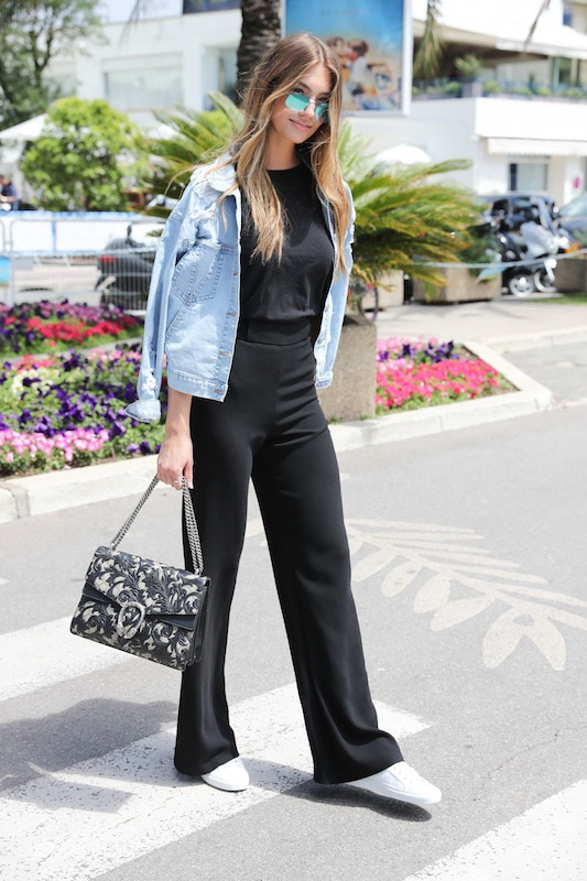 Lorena Rae wearing a black crew neck top, black wide leg pants, a light wash denim jacket, blue mirrored sunglasses, a printed Gucci shoulder bag, and white low top sneakers
