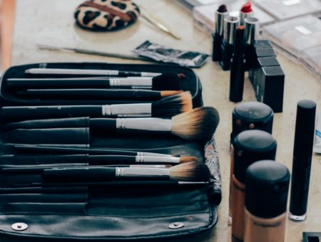 Makeup brushes and foundations laid out on a table