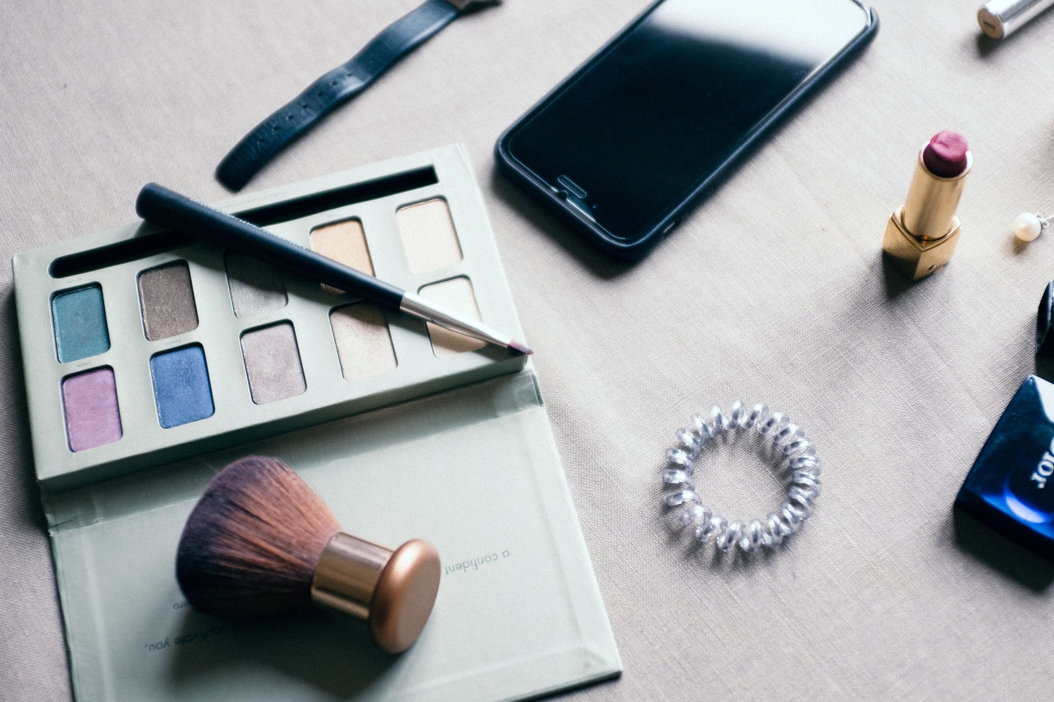 Makeup on a table with iphone and eyeshadow
