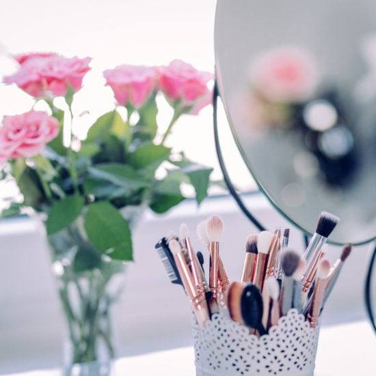 Makeup brushes in a lace pencil holder on a vanity, behind a mirror and pink flowers