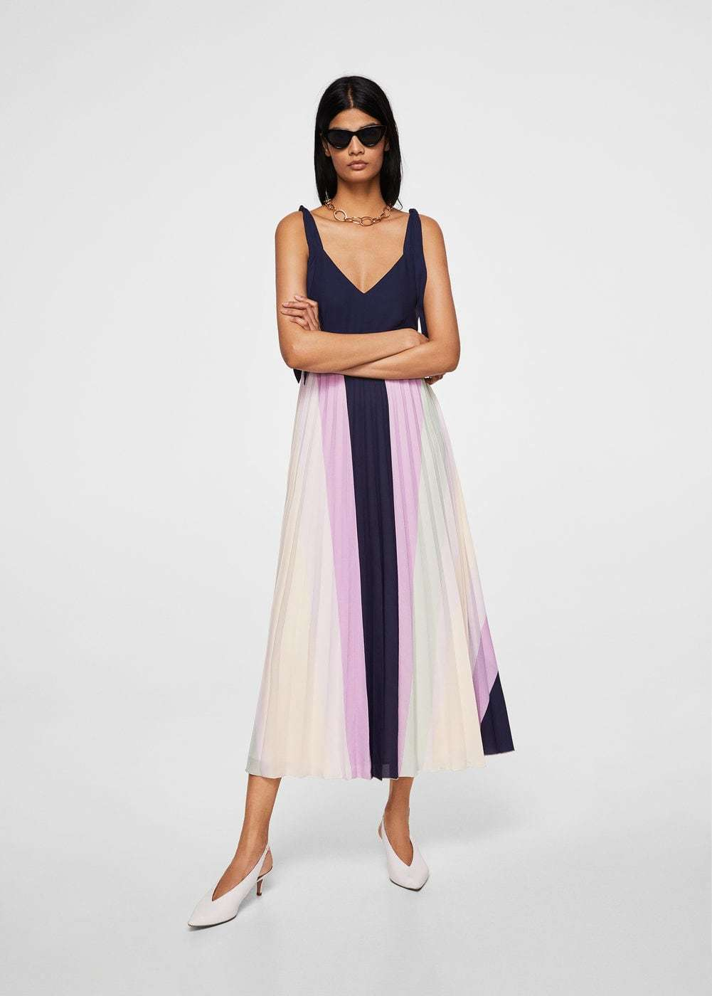 Cute graduation dresses: Sleeveless tie-shoulder midi dress with v-neck and navy blue top with navy blue and pastel lilac, pastel green, and cream-colored pleated skirt