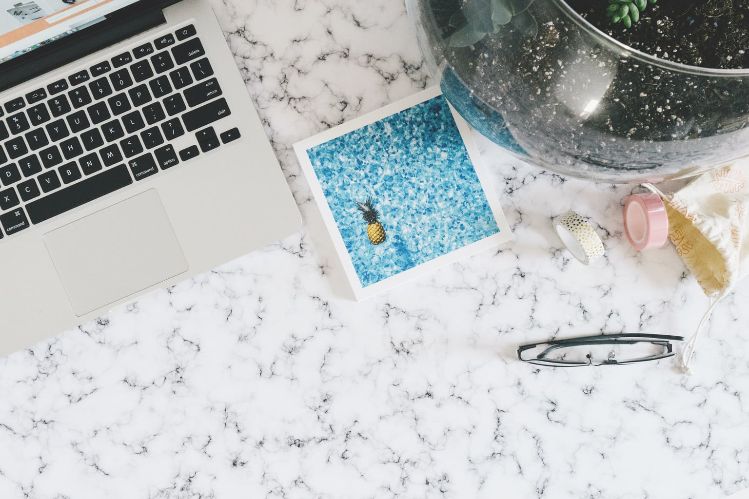 Marble table with laptop, glasses and washi tape