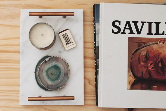 Photo with a marble tray an two books. The tray has a candle, small box, and geode coasters on it.