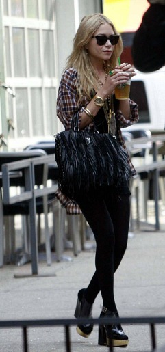 Mary kate olsen wearing a plaid shirt and fringed bag