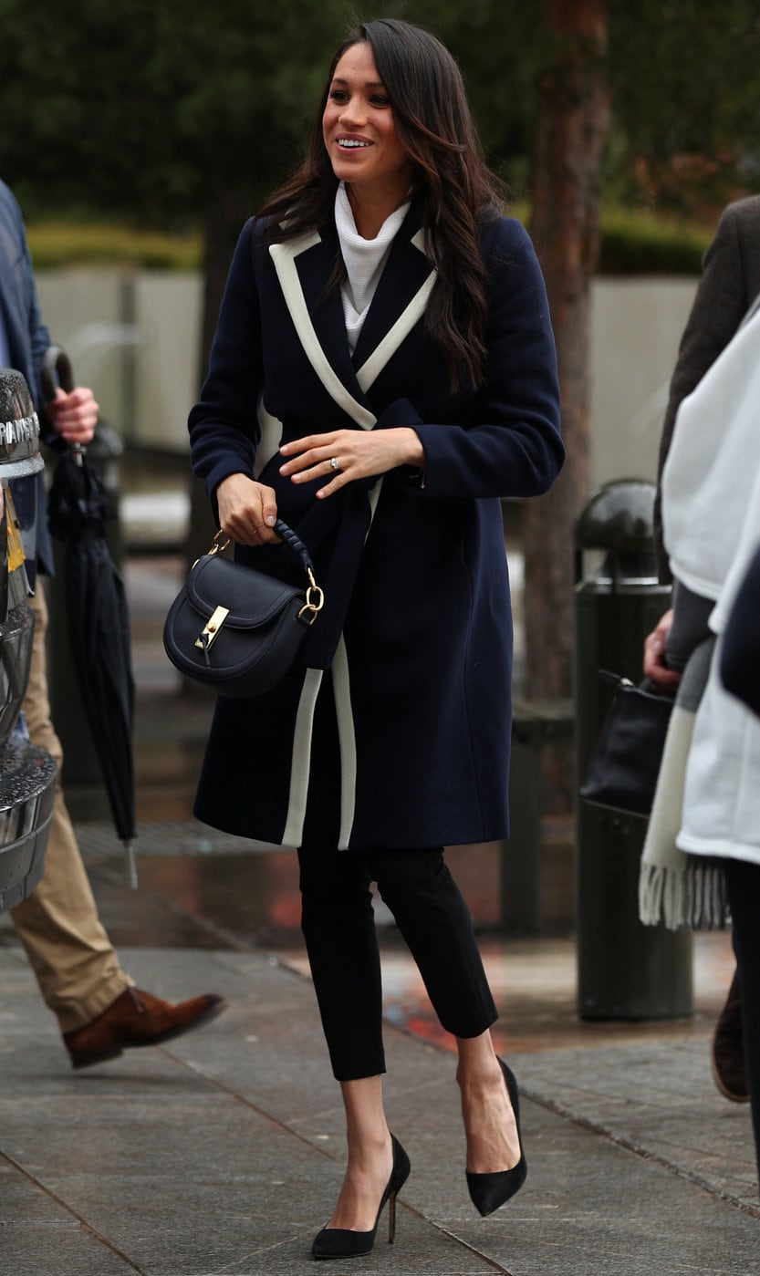 Meghan Markle wearing a navy blue coat with white collar lapel detailing, a white turtleneck sweater, simple black pumps, and a black and gold handbag