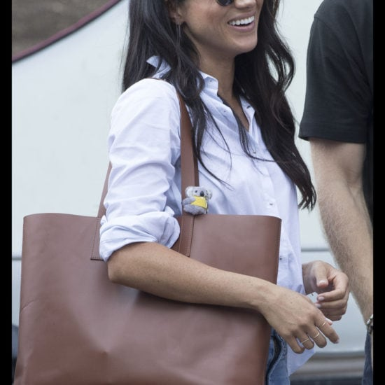 Meghan Markle at the Invictus Games in a blue button down shirt, a brown tote bag, and simple jeans with tortoiseshell sunglasses