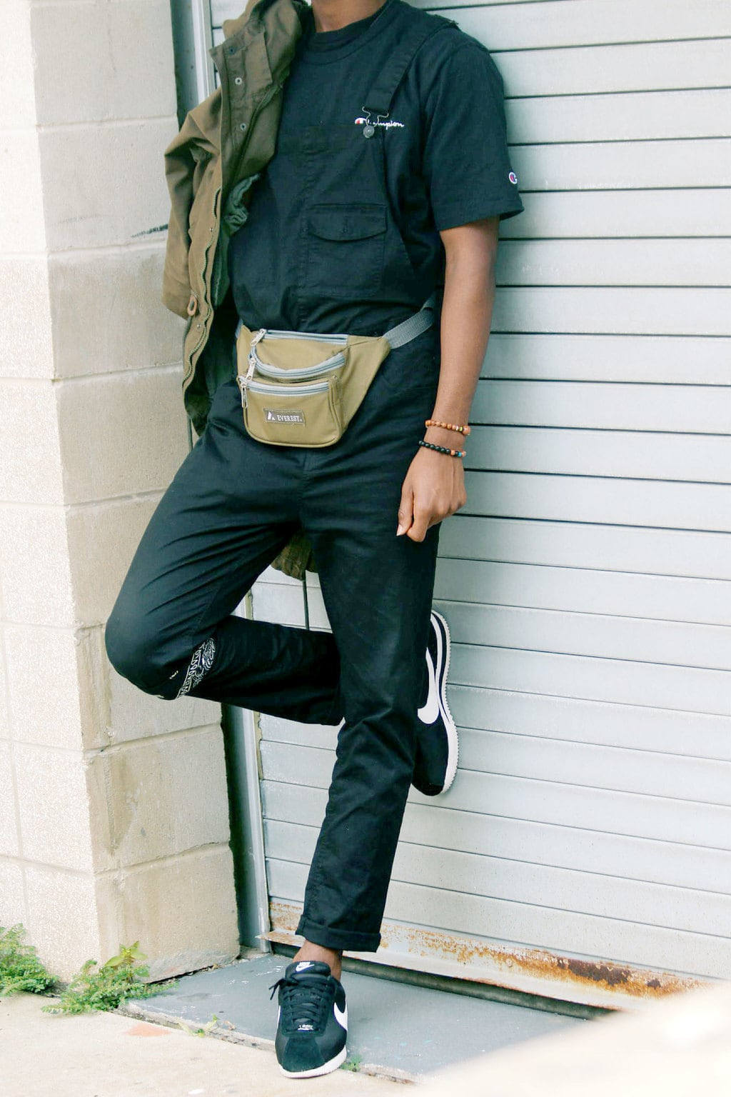 Men's fashion at University of South Florida: Student Karon sports a light brown fanny pack with a black Champion tee and black overalls. He wears a bandana around his leg.