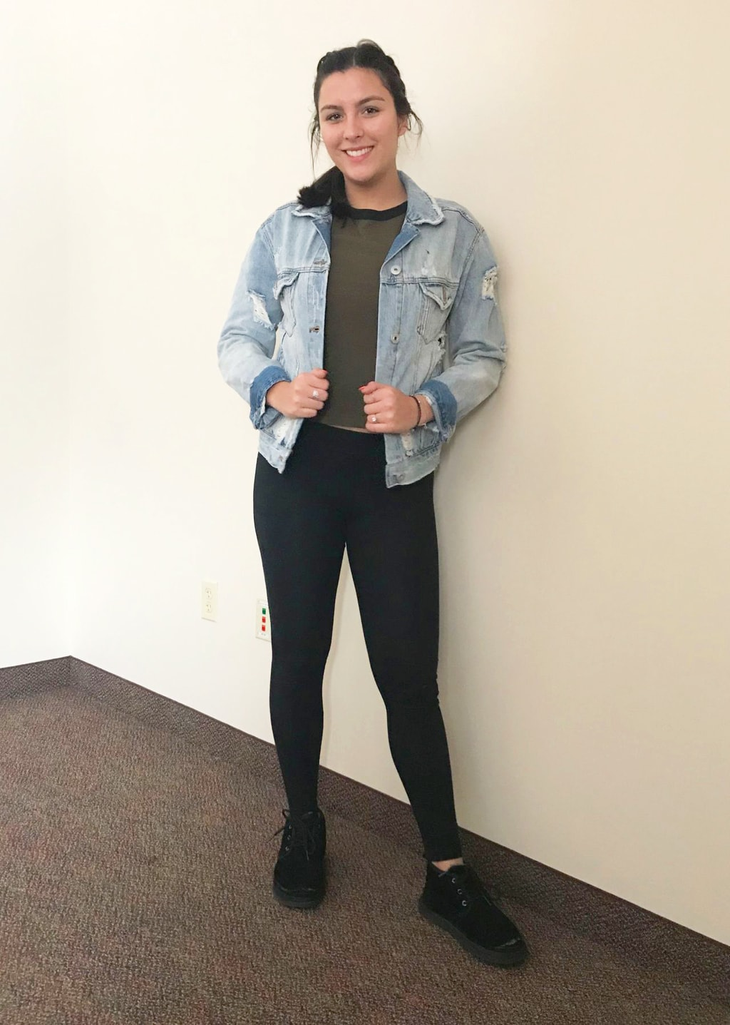 Mercyhurst fashion: Mercyhurst University student Arianna looks is comfortable in her olive green crop top with a black neckline, light-wash distressed denim jacket with the cuffs rolled up, black leggings, and black casual lace-up sneakers.