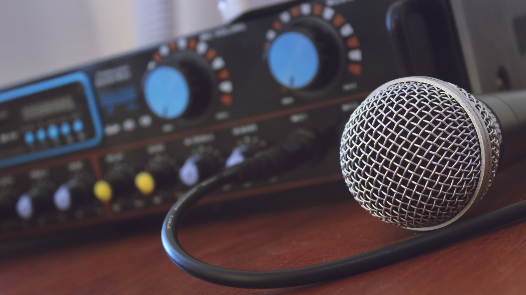 A microphone is set on a table, plugged into amplifier