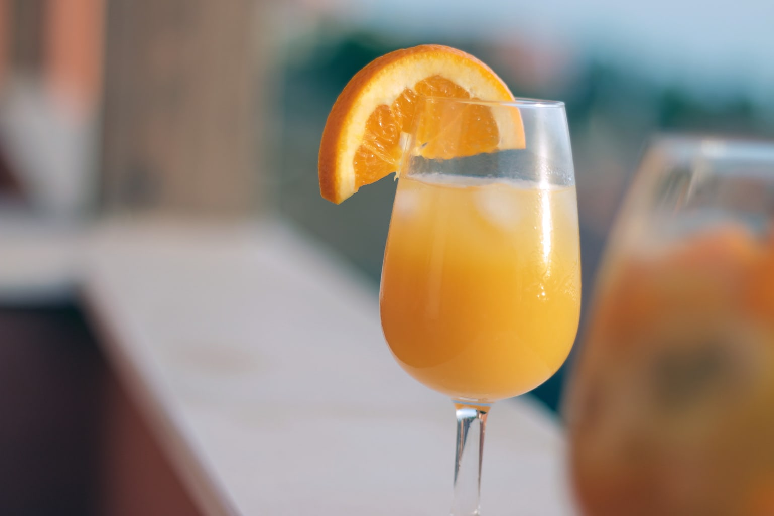 A mimosa in a glass with an orange wedge