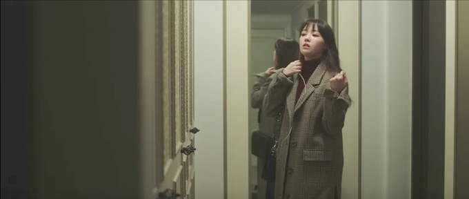 Minah Eleven Degrees music video - shot of Minah wearing a burgundy turtleneck with a brown coat over top