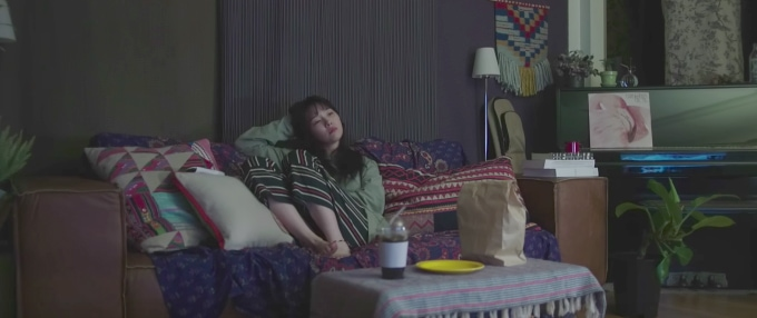 Minah Eleven Degrees music video - shot of Minah on the couch wearing a green top and striped pants
