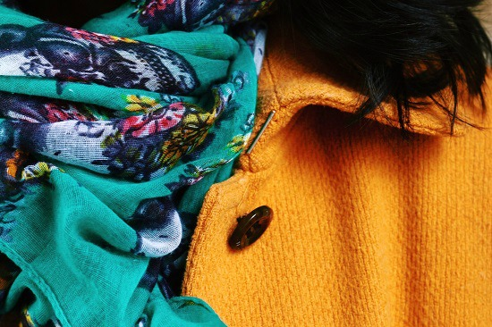 mustard yellow coat and teal scarf